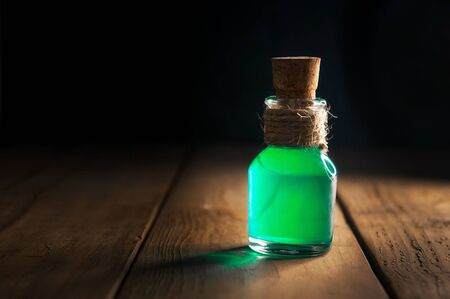 Green poison magic bottle on black and wooden background. Copy space. Selective focus