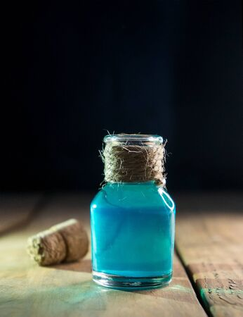 Blue magic liquid in bottle on black and wooden background. Selective focus