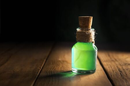 Potion in magic bottle on black and wooden background. Copy space. Selective focus