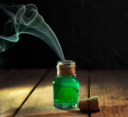 Green toxic water with smoke in magic bottle on black and wooden background. Selective focus
