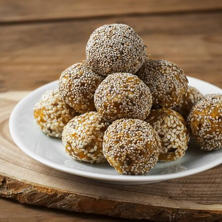 Raw healthy vegetarian and vegan food. Organic snack bites with dried fruits, nuts and honey. Energy balls. Фото со стока