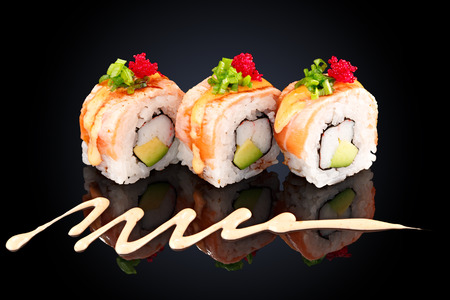 Roll with eel, crab, avocado, cream cheese and spicy sauce on a black background Stock Photo
