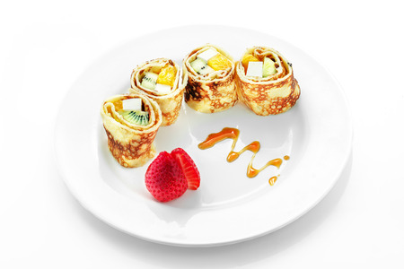Fruit roll in pancake, kiwi, strawberry, apple, an orange on a white background