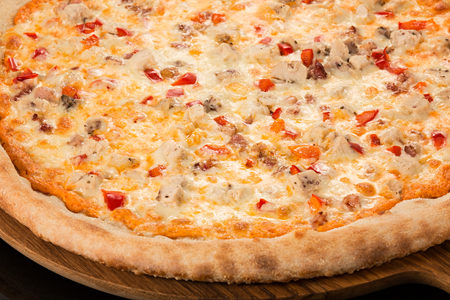 Pizza Spicy, spicy sauce, mozzarella, bacon, chicken, bell peppers, Parmesan on a black background Фото со стока