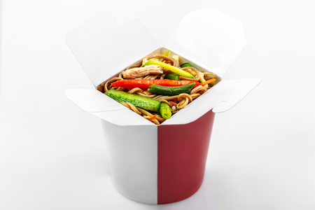 Chinese buckwheat noodles wok vegetables and chicken in box white background