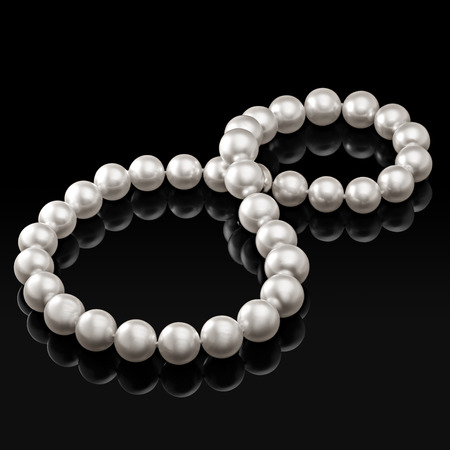Luxury white pearl necklace on a black background with glossy reflection.