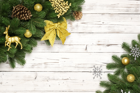 Christmas decorative background border with red and gold bauble decorations, gold star, deer, christmas tree toy, spruce pine, pine cones, fir branches on white wood rustic with copy space. Flat lay.