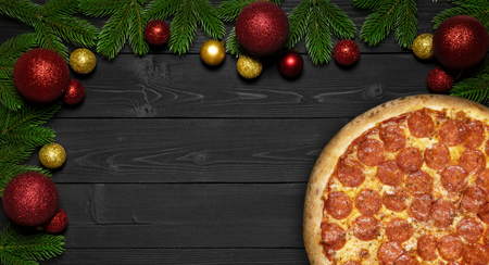Christmas Pizza  on a black wooden background. 스톡 콘텐츠