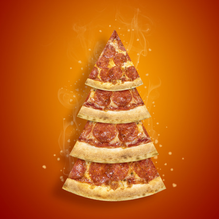 Christmas promotion flyer with pepperoni pizza slice in shape of Christmas tree on orange background. Stock Photo