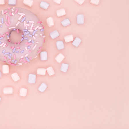 Donut and marshmallow sweet dessert with colorful sprinkles flat lay on pastel coral paper background. Doughnut minimal concept. Copy space. Imagens