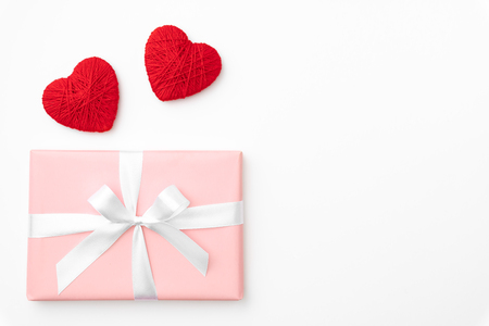 Valentine day idea composition: pink or coral gift box with white ribbon and small red hearts on white background. Top view. Love day concept flat lay.
