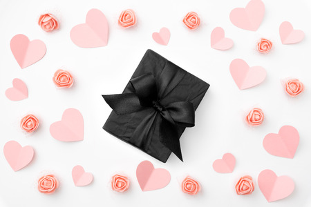 Valentines day composition. Love Day floral background with coral or pink flowers rose, coral paper small hearts, black gift box flat lay. Mothers day, 8 March Women day. Top view.