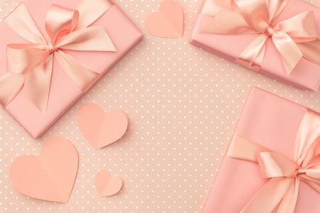 Valentine day decoration gift box with ribbon and small coral hearts on living coral background. Top view. Love day concept flat lay.