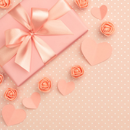 Valentines day flower composition on living coral background with coral flowers rose, paper small hearts, gift box flat lay. Mothers day, 8 March Women day. Top view. Banco de Imagens
