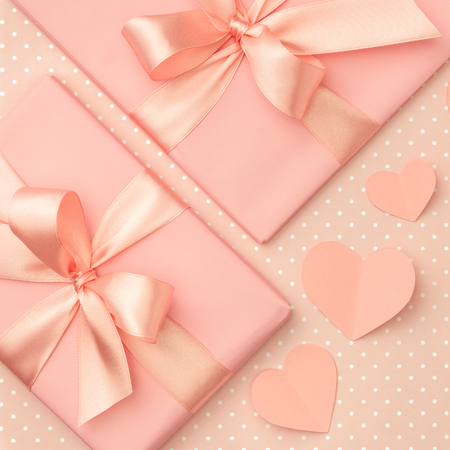 Valentine day idea composition: pink or coral present box with ribbon and small hearts on living coral background. Top view. Flat lay. Banco de Imagens