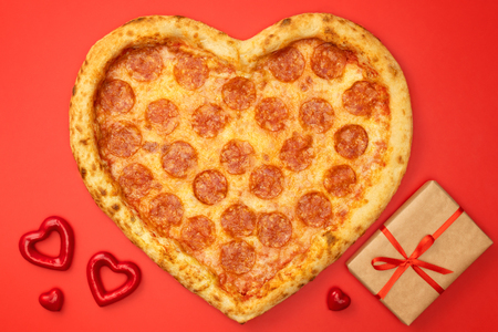 Heart shaped pizza pepperoni for Valentines day with gift box on red paper background.