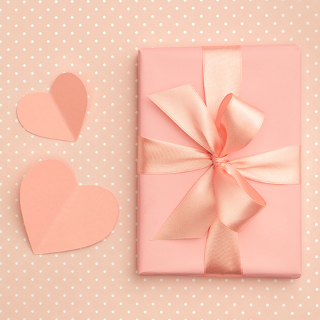 Valentine day idea composition: pink or coral gift box with ribbon and small hearts on living coral background. Top view. Flat lay.