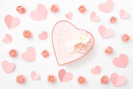 Valentine's day greeting card with decorated paper heart coral or pink rose flowers and  heart shape coral gift box isolated on white background. Top view. Flat lay.