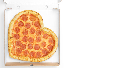 Pizza Heart Shape top view in cardboard box for delivery Valentine Day with copy space isolated on white background. View from above. Valentin Day concept. 写真素材