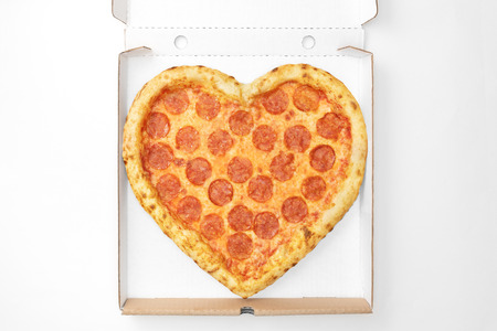 Pizza Heart Shape top view in cardboard box for delivery Valentine Day isolated on white background. View from above. Valentines Day concept pizza delivery, template for your design.
