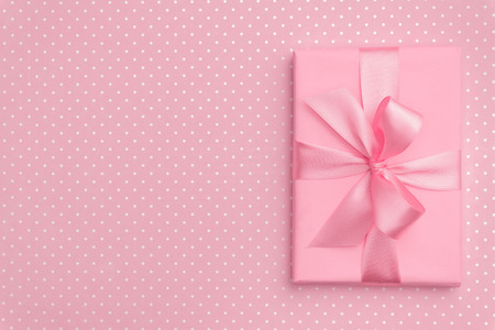Gift box with pink ribbon bow on pink speckled background top view. Holiday concept, birthday gift, New year or Christmas gift box presents Xmas. Congratulations with copy space. Flat Lay. Stockfoto - 125492824