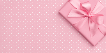 Gift box with pink ribbon bow on pink speckled background top view. Holiday concept, birthday gift, 8 march or Women day, gift box holiday Mothers day. Greeting card with copy space. Flat Lay.
