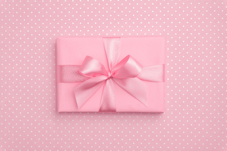 Gift box with pink ribbon bow on pink speckled background top view. Holiday concept, birthday gift, New year or Christmas gift box presents Xmas. Congratulations with copy space. Flat Lay.