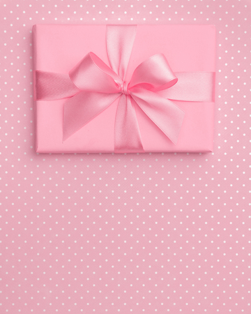 Gift box with pink ribbon bow on pink speckled background top view. Holiday concept, birthday gift, 8 march or Women day, gift box presents holiday Mothers day. Greeting card with copy space. Flat Lay