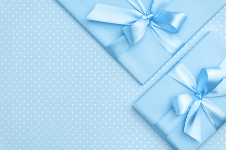 Gift box with blue ribbon bow on blue speckled background top view. Holiday concept, birthday gift, 8 march or Women day, gift box holiday Mothers day. Greeting card with copy space. Flat Lay.