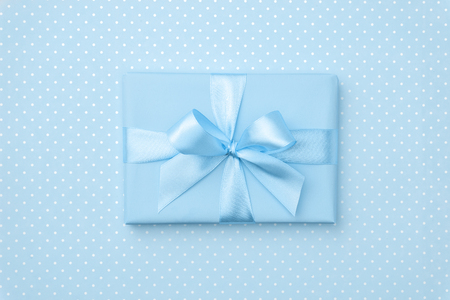 Gift box with blue ribbon bow on blue background top view. Holiday concept, birthday gift, New year or Christmas gift box presents Xmas holiday. Congratulations with copy space. Flat Lay.