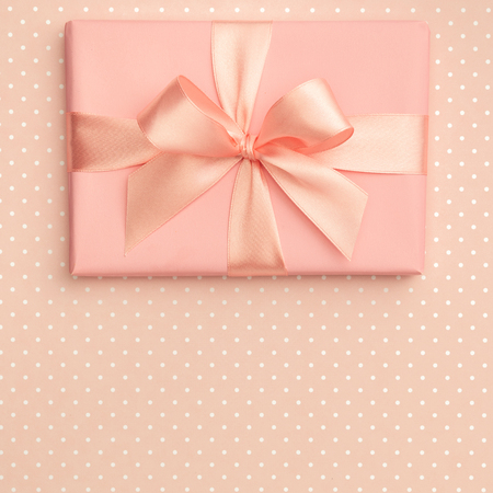 Gift box luxury top view on living coral background with speckled, decorated with bow, creating festive atmosphere. Template used for 8 march women day, Mother day presents, gift cards. Flat lay.