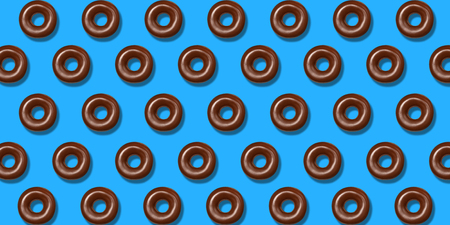 Creative pattern chocolate donuts flat lay on pastel blue background. Minimal sweet food concept. Surreal brown doughnuts cake top view for bakery. Abstract summer donut dessert.