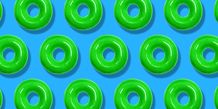 Creative pattern green donuts flat lay on pastel blue background. Minimal sweet food concept. Surreal doughnuts cake top view for bakery. Abstract summer donut dessert.