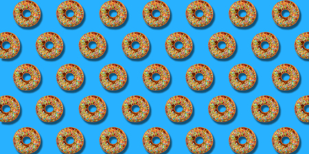 Creative pattern donuts colorful flat lay on pastel blue background. Minimal sweet food concept. Surreal doughnuts cake top view for bakery. Abstract summer donut dessert. Stockfoto