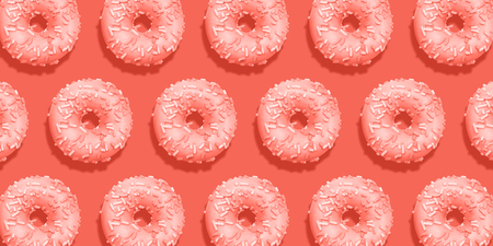 Creative pattern donuts flat lay on pastel coral background. Minimal sweet food concept. Surreal doughnuts cake top view for bakery. Abstract summer donut dessert. Living coral trend color 2019.