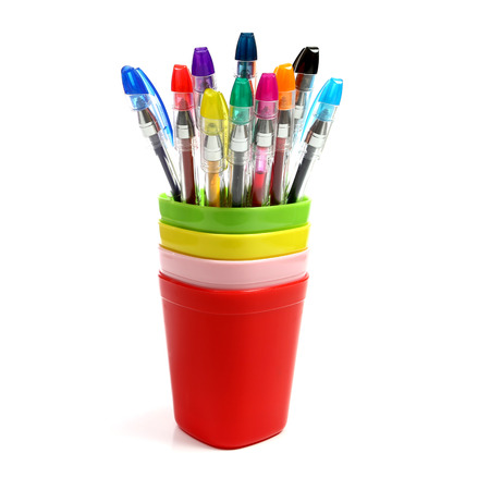 the colorful pen in colorful mugs on white background