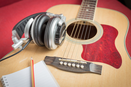 Headphone and Notebook and pencil on guitar for writing music Banco de Imagens