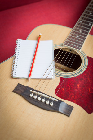 Notebook and pencil on guitar for writing music Banco de Imagens