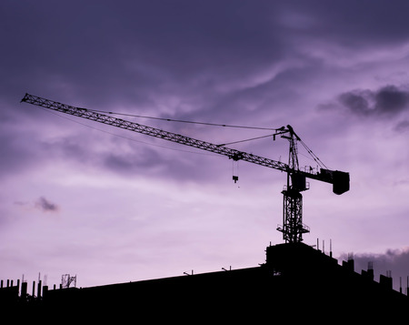 Silhouette of cranes on sunset sky background at construction site