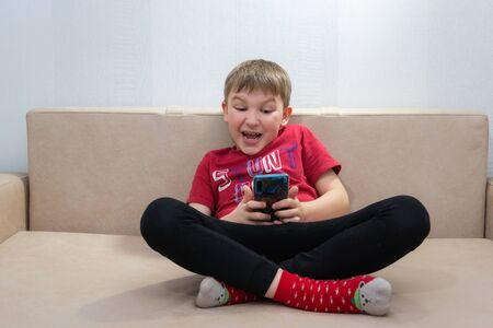 The boy in the red shirt and red socks sitting on sofa and looks in the phone Standard-Bild