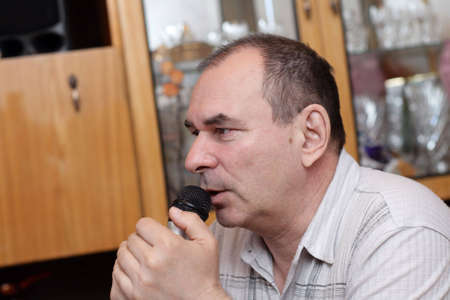 The man with microphone at home, karaoke Stock Photo - 3190100