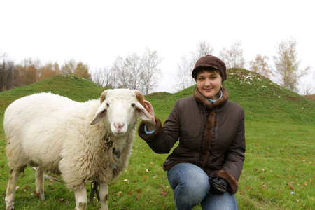 The girl poses with white sheep on lawn Stock Photo - 3716413