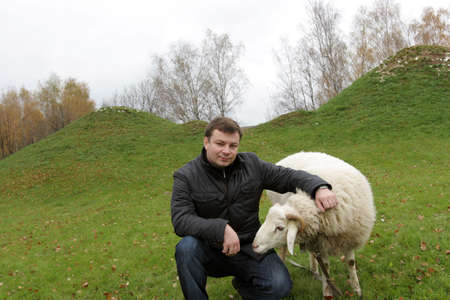 The man poses with white sheep on lawn Stock Photo - 3734793