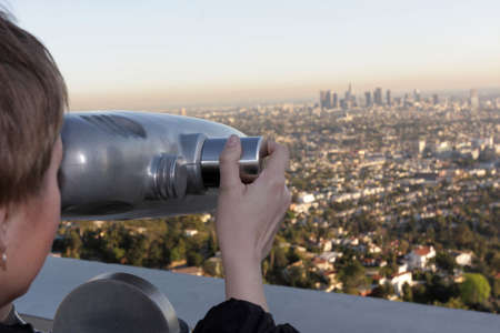 The girl views Los Angeles by telescope photo