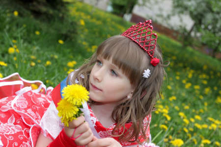 The girl in red dress with dandelions on lawn photo
