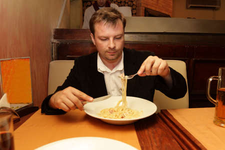 The man eats spaghetti in a italian restaurant photo