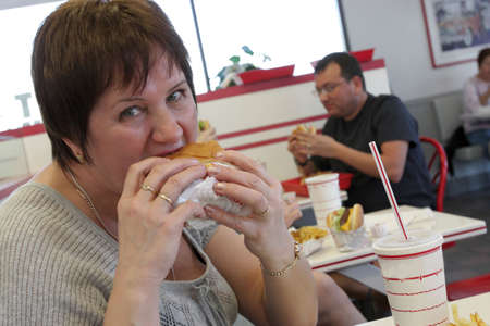 The hungry woman eats burger in a snack bar Stock Photo