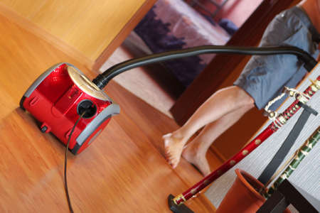 The vacuum cleaner when in use at home photo