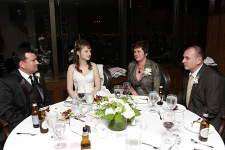 receptions: Newlyweds and their parents in wedding restaurant
