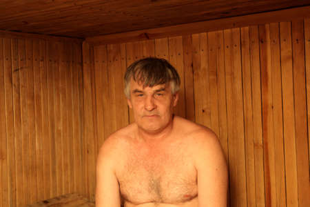 The mature man poses in a Finnish sauna photo
